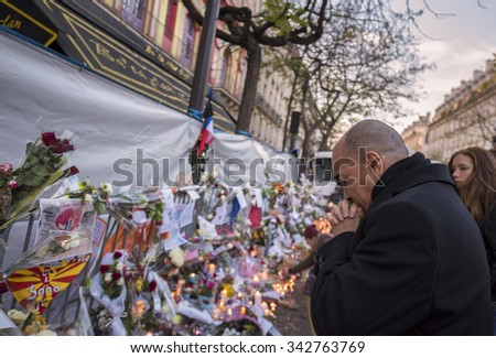 PARIS, FRANCE - NOVEMBER 23, 2015 :  A man pray in front of the theater Le Bataclan in tribute to victims of the Nov. 13, 2015 terrorist attack in Paris at the Bataclan. - stock photo