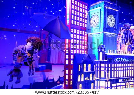 PARIS, FRANCE - NOVEMBER 23, 2014: Colorful Christmas decoration (doll flying with umbrella in London sky) by Burberry in windows of Printemps department store attracts Parisian children and tourists. - stock photo