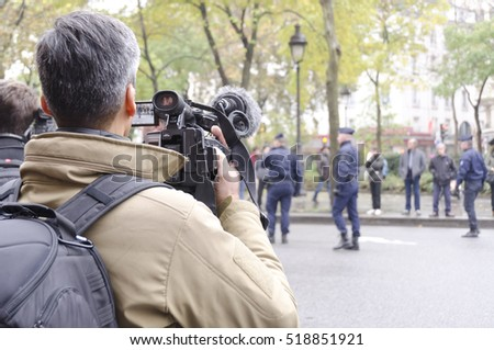 Paris, France - November 13, 2016: Journalist filming the police around the Bataclan during the tribute ceremony