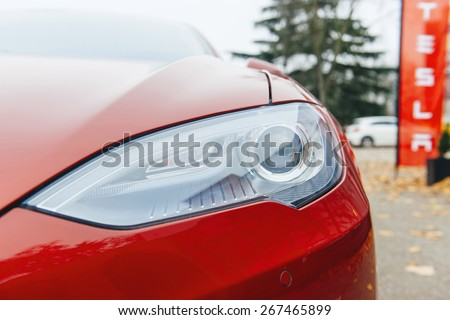 PARIS, FRANCE - NOVEMBER 29: Tesla Model S head light of a red electric car in Paris, France. Tesla is an American company that designs, manufactures, and sells electric cars - stock photo