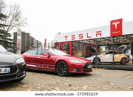 PARIS, FRANCE - NOVEMBER 29: Tesla Model S showroom and two luxury tesla cars outside and one inside. Tesla is an American company that designs, manufactures, and sells electric cars - stock photo