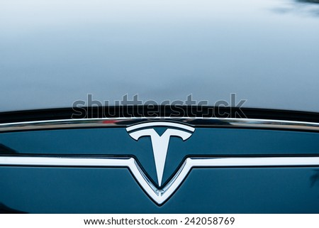 PARIS, FRANCE - NOVEMBER 29, 2014:  The Tesla Motors Inc. badge and logo are seen below the hood of the Model S electric vehicle displayed at the company's showroom in Paris, France - stock photo