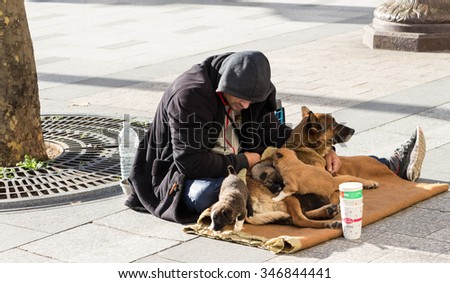 Paris; france-November 22, 2015: The unidentified homeless is begging  with dogs on Champs Elysees avenue in Paris, France. - stock photo