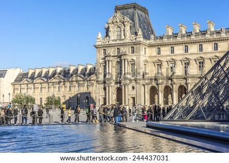 PARIS, FRANCE - NOVEMBER 12, 2014: View of Louvre building at Louvre Museum courtyard with pyramid and fountain. Louvre Museum is one of the largest and most visited museums worldwide. - stock photo