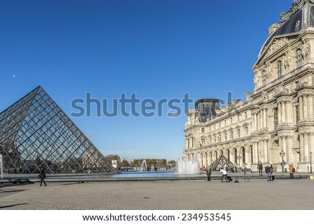 PARIS, FRANCE - NOVEMBER 12, 2014: View of pyramid and fountain at courtyard of Louvre Museum. Louvre Museum is one of the largest and most visited museums worldwide. - stock photo