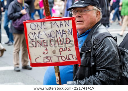 """PARIS, FRANCE - OCT. 5, 2014: A man holds a sign during an anti-gay rights protest in Paris, which says """"One Man, One Woman, One Child and That's it"""". The manifestation drew around 100,000 people. - stock photo"""