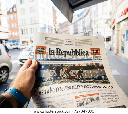 PARIS, FRANCE - OCT 3, 2017: Man buying Italian La Repubblica newspaper with socking title photo at press kiosk about the 2017 Las Vegas Strip shooting in United States 60 fatalities and 527 injuries