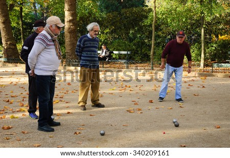 PARIS, FRANCE - OCTOBER 31, 2015: A group of senior men playing petanque in Jardin du Luxembourg (Luxembourg Garden). Luxembourg Garden is one of the most popular Parisian parks. - stock photo