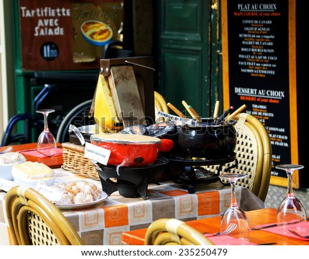 PARIS, FRANCE - OCTOBER 5, 2014: Fondue Savoyarde and Raclette displayed (to attract customers) in typical traditional restaurant. Latin Quarter known for its restaurants serving traditional dishes.  - stock photo