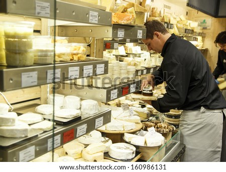 PARIS, FRANCE - OCTOBER 19: French cheese shop near Maubert-Mutualite in Paris with dozens of kinds of French chees and a worker arranging them on October 19th 2013 in Paris, France - stock photo
