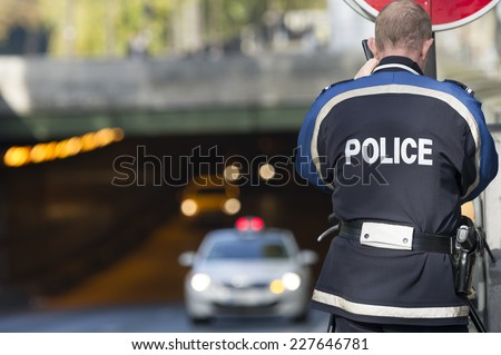 PARIS, FRANCE - OCTOBER 31, 2014 :French policeman controls speed with a mobile radar Pro laser 4 - stock photo