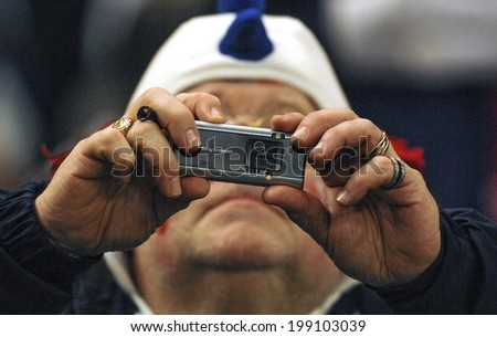 PARIS, FRANCE-OCTOBER 14, 2007: french rugby fan taking picture with an handy camera during the Rugby World Cup match France vs England, in Paris. - stock photo