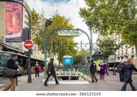 PARIS, FRANCE - OCTOBER  9, 2014:  Picture here is a Metro subway entrance street scene in Paris, France with many people visible.   - stock photo