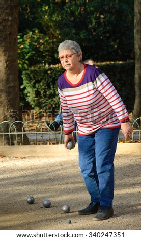 PARIS, FRANCE - OCTOBER 31, 2015: Senior woman playing petanque in Jardin du Luxembourg (Luxembourg Garden). Luxembourg Garden is one of the most popular Parisian parks. - stock photo