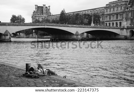 PARIS, FRANCE - OCTOBER 4, 2014: Unidentified young man laying on his skateboard and reading on Seine bank near Louvre museum. Seine embankment is very popular promenade at weekends. - stock photo