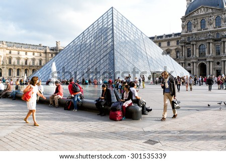 PARIS, FRANCE - OCTOBER 14, 2014: View of pyramid and fountain at courtyard of Louvre Museum. Louvre Museum is one of the largest and most visited museums worldwide. - stock photo