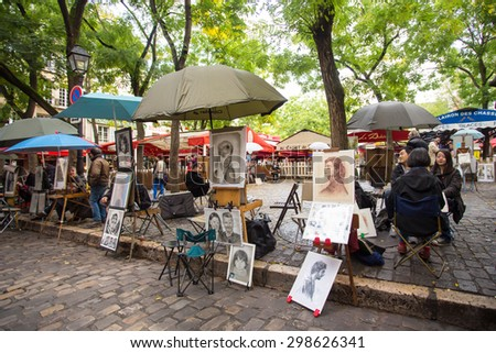 PARIS, FRANCE - OCTOBER 9, 2014:  View of  the artists square in Place du Tertre in the Montmartre district in Paris France with people visible.  - stock photo