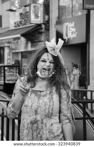 PARIS, FRANCE - OCTOBER 3, 2015: Young woman in zombie bride dress makes victory sign during Zombie parade at Place de la Republique. Zombie Walk is an annual event in Paris. - stock photo