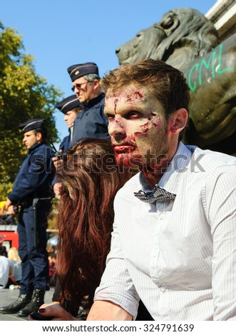 PARIS, FRANCE - OCTOBER 3, 2015: Zombie couple participating in Zombie parade at Place de la Republique and police force keeping order at background. Zombie Walk is an annual event in Paris. - stock photo