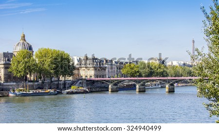 PARIS, FRANCE, on AUGUST 29, 2015.Arts Bridge (fr. pont des Arts or passerelle des Arts) - the first iron bridge of Paris through the river Seine. Skyline on Seine Embankment.  - stock photo