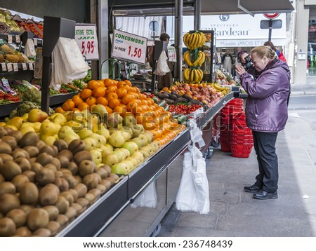 Paris, France, on May 4, 2013. The elderly tourist photographs vegetables and fruit on a counter of the street market