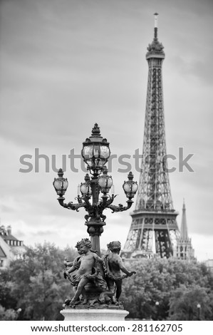 Paris France Pont Alexandre III Bridge statues of cherubs on street lamp with Eiffel Tower in black and white - stock photo