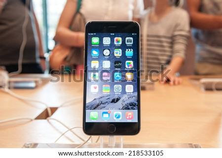 PARIS, FRANCE - SEPTEMBER 20, 2014: An iPhone 6 smartphone stands on display inside an Apple Store with a mother and her daughter admiring other iPhone 6 - stock photo