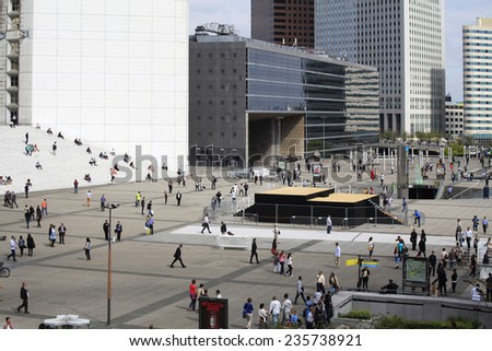 PARIS, FRANCE - SEPTEMBER, 2, 2014. Corporate office buildings in the financial center La Defense, Paris. There are a lot of people walking on the square before the Grande Arche.  - stock photo