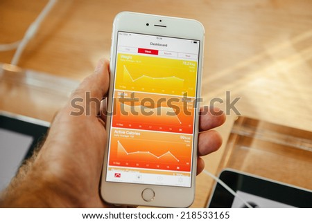 PARIS, FRANCE - SEPTEMBER 20, 2014: Hand holding a iPhone 6 Plus displaying healthcare dashboard of the new Health App during the sales launch of the latest Apple Inc. smartphones at the Apple store - stock photo