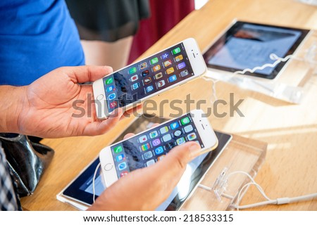 PARIS, FRANCE - SEPTEMBER 20, 2014: Man comparing the new Apple iPhone 6 and iPhone 6 Plus during the sales launch of the latest Apple Inc. smartphones at the Apple store in Paris, France - stock photo