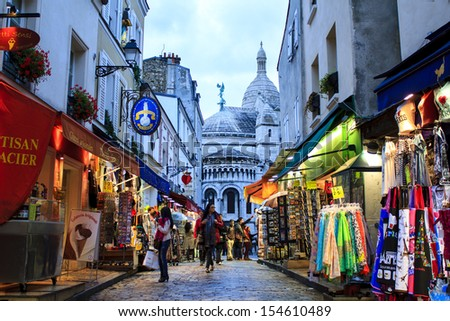 PARIS, FRANCE - SEPTEMBER 16 : Montmartre by twilight - shopping street near Sacre Coeur with tourists and Parisians walking around on September 16th 2013 in Paris, France - stock photo