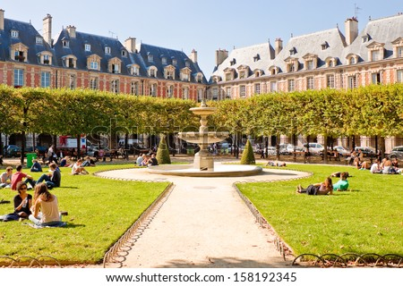 PARIS, FRANCE - SEPTEMBER, 24: People relaxing on green lawns of the famous Place des Vosges - the oldest planned square in Paris located in Marais district on September 24, 2013 in Paris. - stock photo