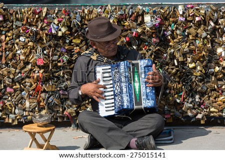 PARIS, FRANCE - SEPTEMBER 8, 2014: Pont de l'Archeveche  An accordion player sitting on a bridge in Paris and plays French songs. Behind him is the bridge railing, full of thousands of love locks.  - stock photo