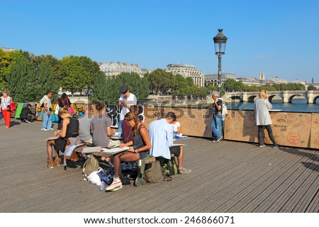 PARIS, FRANCE - SEPTEMBER 10 2014: Students doing plein air sketches on the Pont des Artes. This pedestrian bridge over the Seine is very popular with students, artists, photographers and lovers. - stock photo