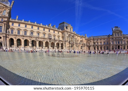 PARIS, FRANCE - SEPTEMBER 8, 2012: The entrance to Louvre -  glass pyramid fountain. Tourists resting on granite fence fountain. Traces in the sky jet. Picture taken Fisheye lens - stock photo