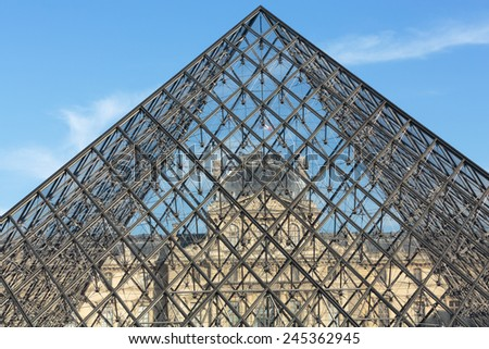 Paris, France - September 9, 2014: The Glass  Pyramid in Louvre Paris, France. It serves as the main entrance to the Louvre Museum. Completed in 1989 it has become a landmark of Paris.  - stock photo