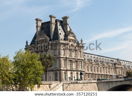 PARIS, FRANCE - SEPTEMBER 9, 2014: The Louvre and  the Seine River in Paris .  Louvre is one of the biggest Museum in the world, receiving more than 8 million visitors each year. Paris,France  - stock photo