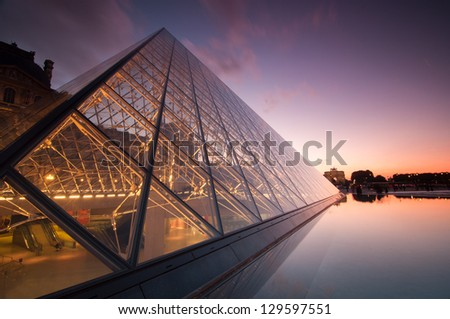 PARIS, FRANCE - SEPTEMBER 28: The Louvre Pyramid at dusk on September 28, 2012 in Paris. It serves as the main entrance to the Louvre Museum. Completed in 1989 and is a landmark of the city of Paris. - stock photo