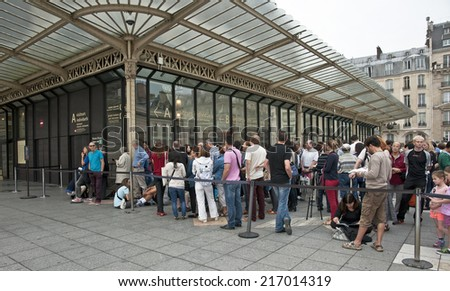 PARIS, FRANCE - SEPTEMBER 7, 2014: Tourist waiting in front of the Musee d'Orsay. Opened in 1986, it houses the largest collection of impressionist and post-impressionist masterpieces in the world.  - stock photo