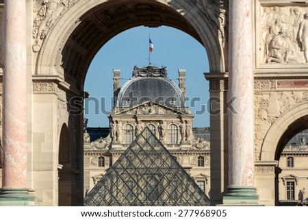 PARIS, FRANCE - SEPTEMBER 9, 2014: Triumphal Arch and Glass Pyramid in Louvre. Louvre is one of the biggest Museum in the world; receiving more than 8 million visitors each year. Paris, France - stock photo