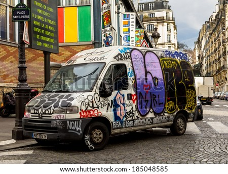 PARIS, FRANCE - 19TH MARCH 2014: A van covered in graffiti in down a street in Paris