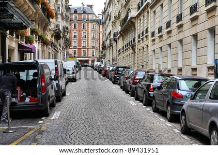 Paris, France - typical old city street. Cars parked along cobblestone way. - stock photo