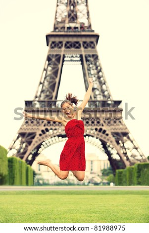 Paris girl at Eiffel Tower jumping happy smiling excited in red summer dress. Joyful young woman on Champs cheerful during vacation / holidays in Paris, France, Europe.