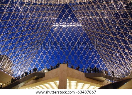 PARIS - JAN 10: Inside the Louvre pyramid on Jan 10, 2008 in Paris. Visitors leaving through the pyramid, built in 1988. The Louvre is the most visited art museum in the world. - stock photo