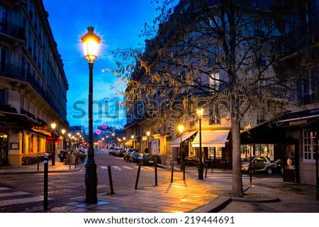 PARIS-JAN 5,2014:Paris street in one of the oldest neighborhoods in the city, the Ile Saint-Louis, with cobblestone streets and charming buildings lit by street lamps. Shot in the blue hour. - stock photo