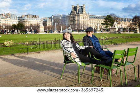 PARIS - Jan. 2, 2014: Smiling tourists rest in the green metal chairs found all over the Tuileries Garden, a grand public park between the Louvre Museum and the Place de la Concorde. - stock photo