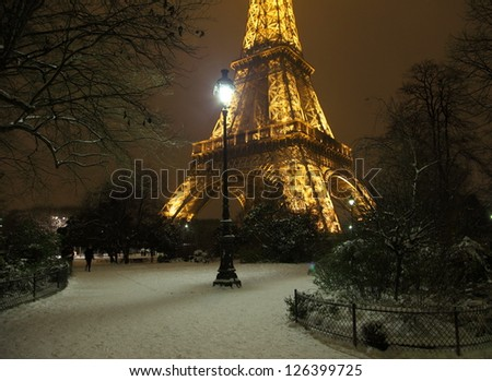 PARIS -JANUARY 20: Romantic snowy park near the Eiffel Tower, January 20, 2013. Snowing is very rare event  in Paris, and Eiffel Tower is particularly beautiful when seeing from snowy parisian parks. - stock photo