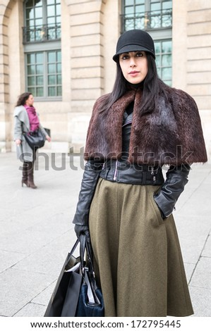 PARIS - JANUARY 23, 2014: Stylish European woman with leather shoulder cape at the Place Vendome. Paris Fashion Week: Haute Couture 2014/2015 is held in Paris from January 20 to 23, 2014.