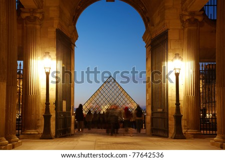 PARIS - JANUARY 1: Tourists in the Louvre look round the Louvre pyramid, January 1, 2010, Paris, France. The glass pyramid of Louvre serves in Napoleon's court yard as a front entrance in Louvre. - stock photo