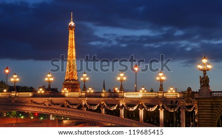 PARIS - JULY 30: Eiffel Tower and Pont Alexandre III on July 30, 2012 in Paris, France. The bridge, with its exuberant lamps, cherubs and winged horses at either end, was built between 1896 and 1900. - stock photo